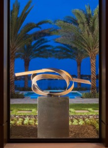 """Jupiter Knot Location: Jupiter, Fl.  Sculpture Size: 20""""X24""""X72"""" Material: Patinated Bronze on Stone base Comment: Residence court yard placement so that it is viewable from all 3 wings of the house & back dropped by pool and water beyond."""